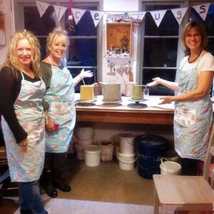 Image of happy students ishowing off their hand built jugs in a pottery class near Bath uk