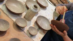 Image of hands putting a glaze on a ceramic bowl before firing, to illustrate a ceramics workshop in wiltshire, near Bath