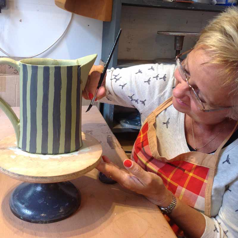 A student painting a handbuilt ceramic jug that she made in a pottery workshop near Bath UK