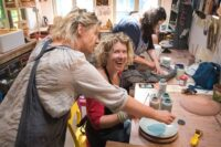 Image of jane demonstrating ceramics and pottery techniques to a laughing student
