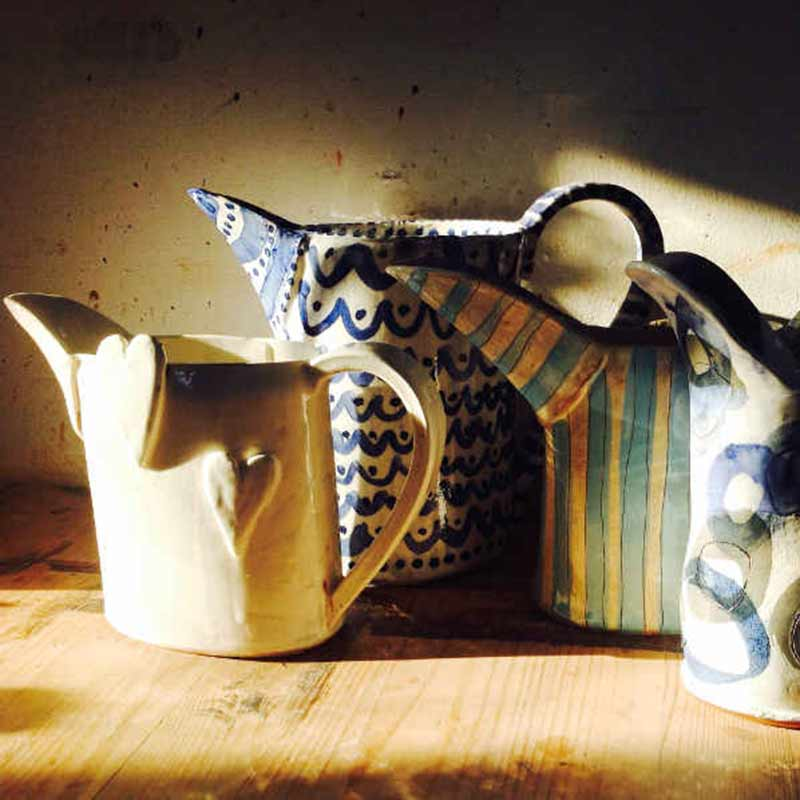 Hand built ceramic jugs with colourful glazes made by students in our ceramic jug making workshop near Bath UK