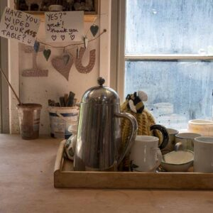 A tray of tea cups and a teapot by the window of Janes ceramics studio during a time for students to come and work independently with clay near holt, wiltshire uk