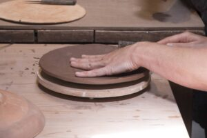 A students hand moulding a ceramic plate out of red clay in one of our workshops