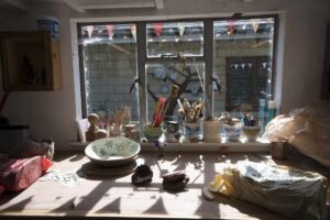 The window of the potttery studio with the sun shining through onto bags of clay and various ceramic creations on the table